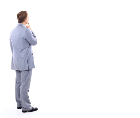 standing against: Full length of young business man standing with arms folded over light wall