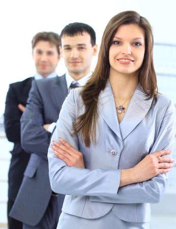 leiterin: junge Frau mit ihrem Team im Hintergrund.