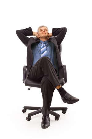 Relaxed homme du milieu des affaires mûr assis sur une chaise isolée sur fond blanc