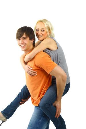 teenaged: Piggybacking - Happy young teenaged couple enjoying themselves against white   Stock Photo