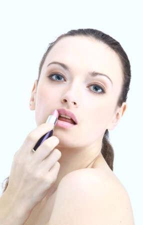 Portrait of beautiful woman applying lipstick using lip concealer brush photo