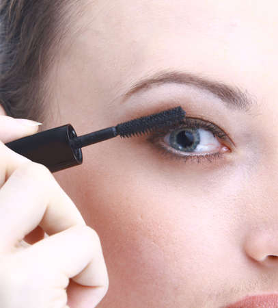 Portrait of pretty young woman applying mascara using lash brush  photo