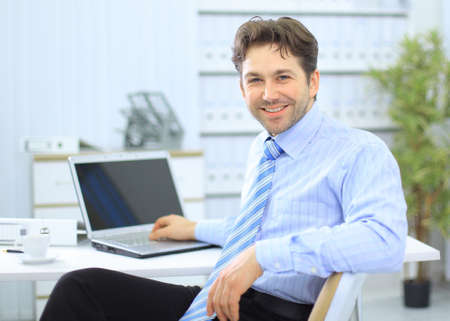 Businessman sitting at office desk working on laptop computer photo