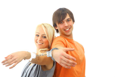 woman handcuffs: Portrait of a young teenage couple smiling against white background