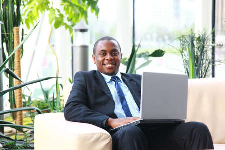 Attractive African American smiling at computer, while sitting at a desk typing on keyboard. Square photo