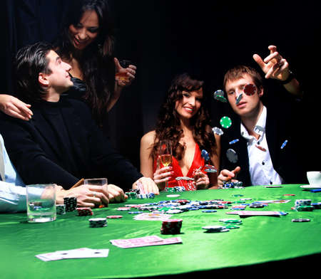 Young man throwing chips on the table while playing cards photo