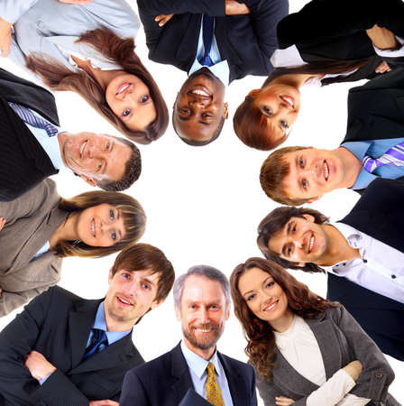 huddle: Group of business people standing in huddle, smiling, low angle view  Stock Photo