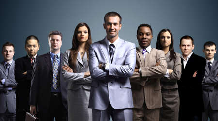 corporation: business team formed of young businessmen standing over a dark background