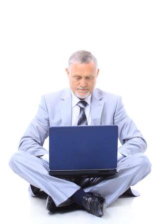 crosslegged: Executive sitting on the floor cross-legged with laptop