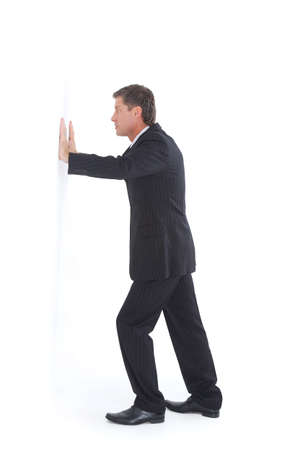 Isolated portrait of a senior business man pushing against the wall photo