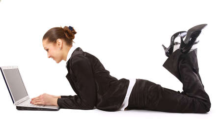 lying down: young woman is lying on the floor and working on a laptop