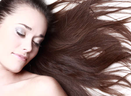 brown hair blue eyes: woman with her hair blowing and smiling