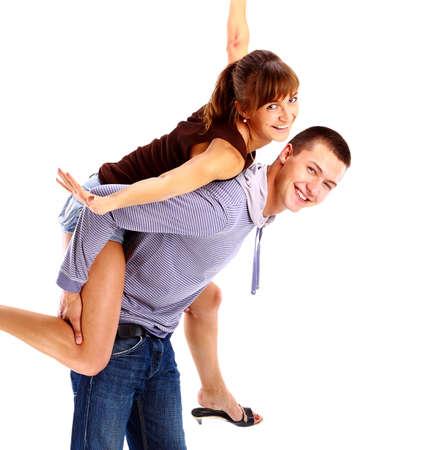 enjoying life: Happy young female enjoying a piggyback ride on boyfriends back against white