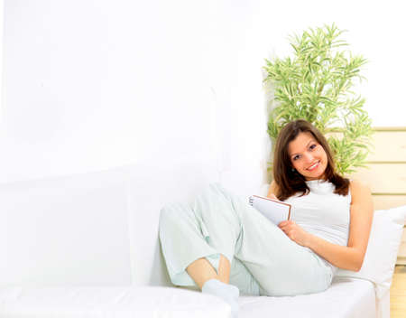 Portrait of a smiling young woman lying on sofa and writing documents  photo