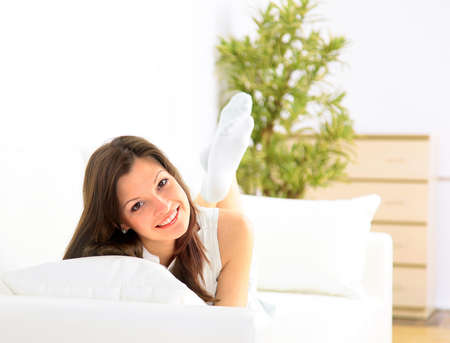 divan: Smiling girl lying down on divan and thinking  Stock Photo