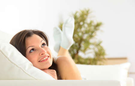 young add: Smiling girl lying down on divan and thinking  Stock Photo