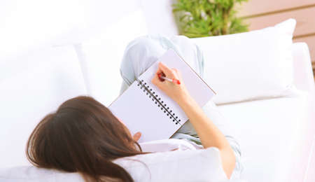 young add: Young businesswoman lying on sofa and reading documents