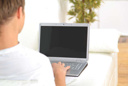 man using computer: Rear view closeup of a young man working of a laptop Stock Photo