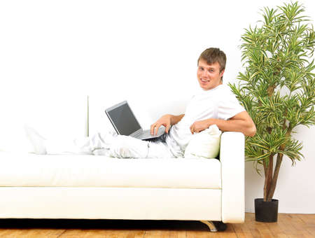 contempory: Smiling young man working on laptop computer at home   Stock Photo