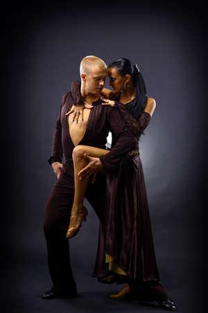 black man white woman: dancers against black background