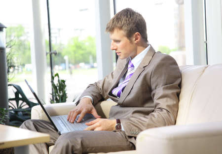 Businessman working on laptop computer at office lobby  photo