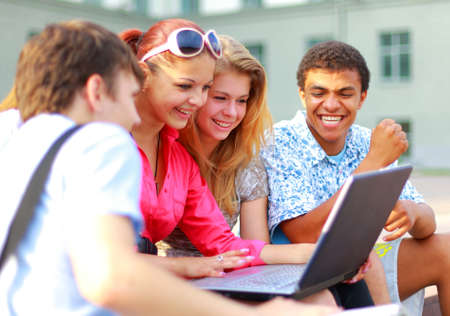 studygroup: Closeup of happy young friends using laptop