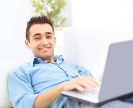 office use: Smiling young man working on laptop computer at home Stock Photo