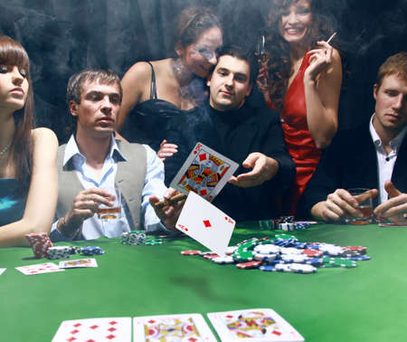 trickery: Stylish man in black suit folds two cards in casino poker at Las Vegas over black