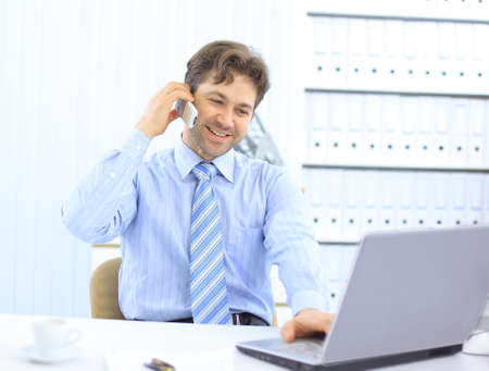 Handsome business guy working on cellphone and laptop together while at work  Stock Photo - 11814149