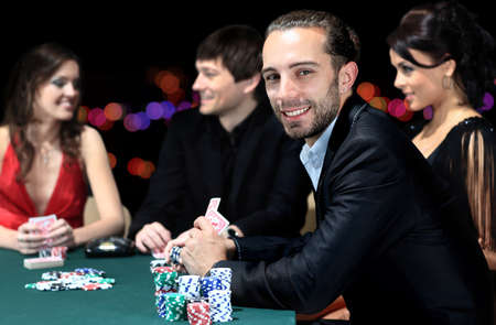 gambling chip: Poker players sitting around a table at a casino Stock Photo