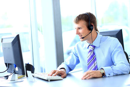 Happy young man working at callcenter, using headset photo