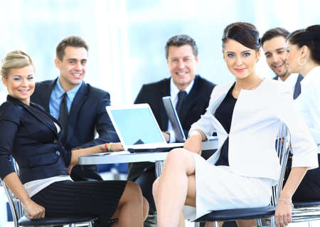 happy business team: Portrait of a cute business woman smiling with people at the back Stock Photo