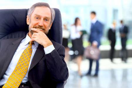 彼のスタッフと事務所でのバック グラウンドで立っている成功するビジネス人