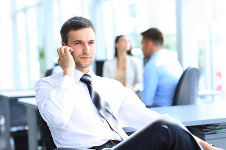 modern businessman: Successful businessman sit at his desk while talking on mobile in office