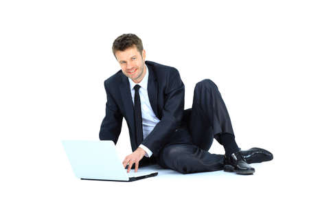 Happy young business man working on a laptop, isolated on white background  photo