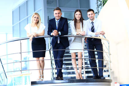 Portrait of positive business group standing on stairs of modern office photo