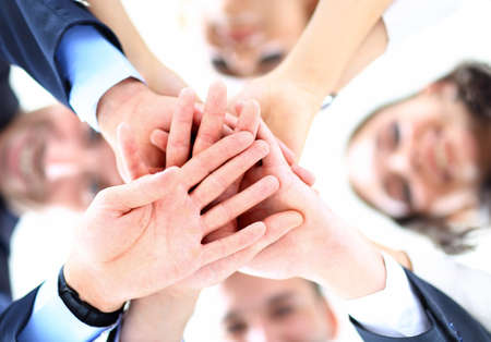 join the team: Small group of business people joining hands, low angle view. Stock Photo
