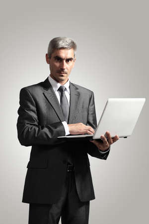 mature businessman: Smiling handsome businessman working with laptop. Isolated over white background Stock Photo