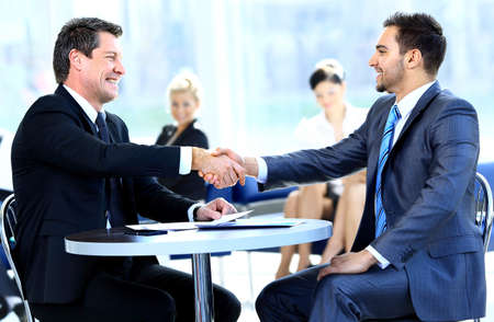 team meeting: Two business colleagues shaking hands during meeting Stock Photo