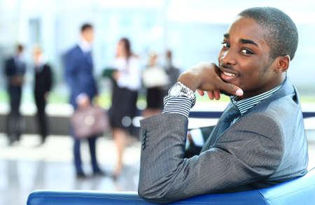 business man laptop: Retrato del hombre de negocios estadounidense con los ejecutivos trabajan en segundo plano