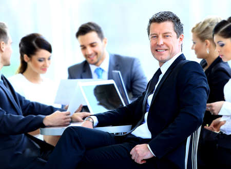 successful business woman: Portrait of mature business man smiling during meeting with colleagues in background Stock Photo
