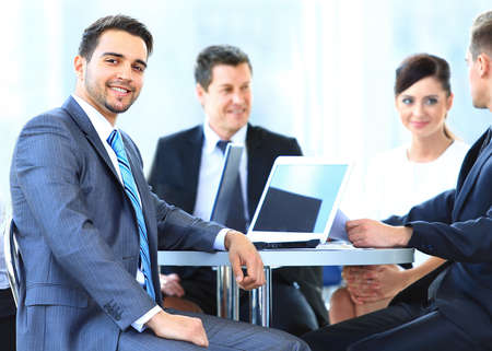 meeting table: Portrait of mature business man smiling during meeting with colleagues in background Stock Photo