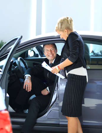 Man buying a car in dealership sitting in his new auto photo
