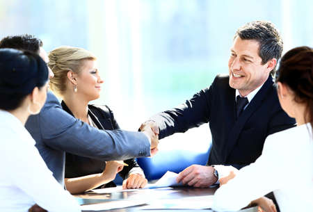 Two business colleagues shaking hands during meeting photo