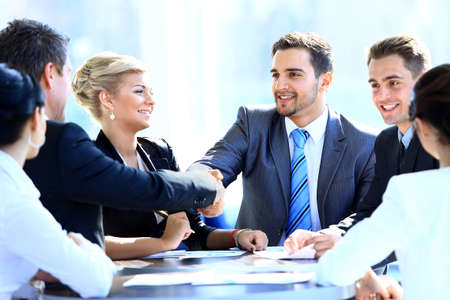 international business agreement: Two business colleagues shaking hands during meeting Stock Photo