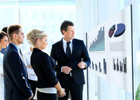 glassboard: Business people having on presentation at office. Businessman presenting on glassboard.