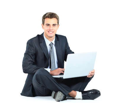 Isolated seated young businessman using a laptop photo