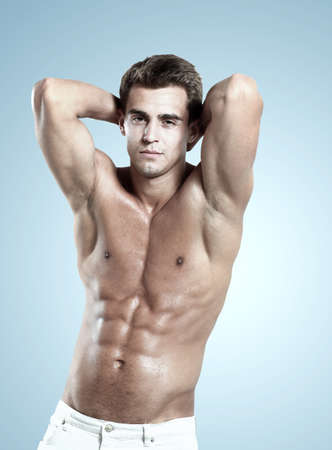 naked man: a young male model posing his muscles