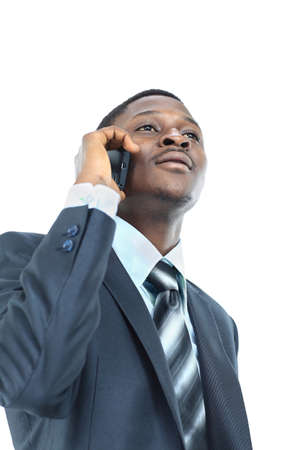 african businessman: Young entrepreneur holding his coat over shoulder while talking on cell phone