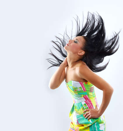 flowing hair: A beautiful young woman with her hair blowing and smiling, in front of a white background